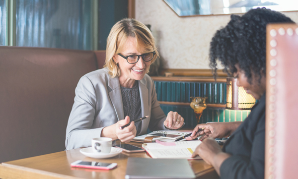 Blond woman in glasses in meeting with a woman with black hair.